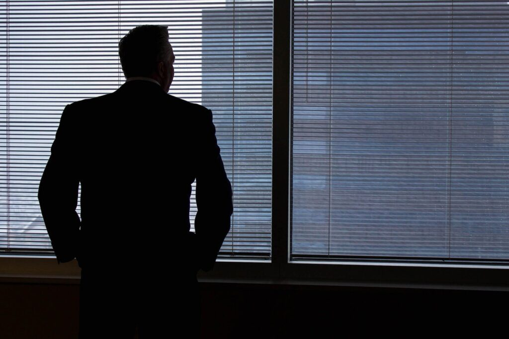 Effective management reporting systems. The silhouette of a man in a suit stands by a window, looking out.