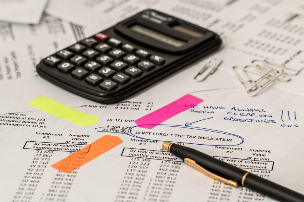 Reducing tax. A calculator and pen are on top of tax documents.