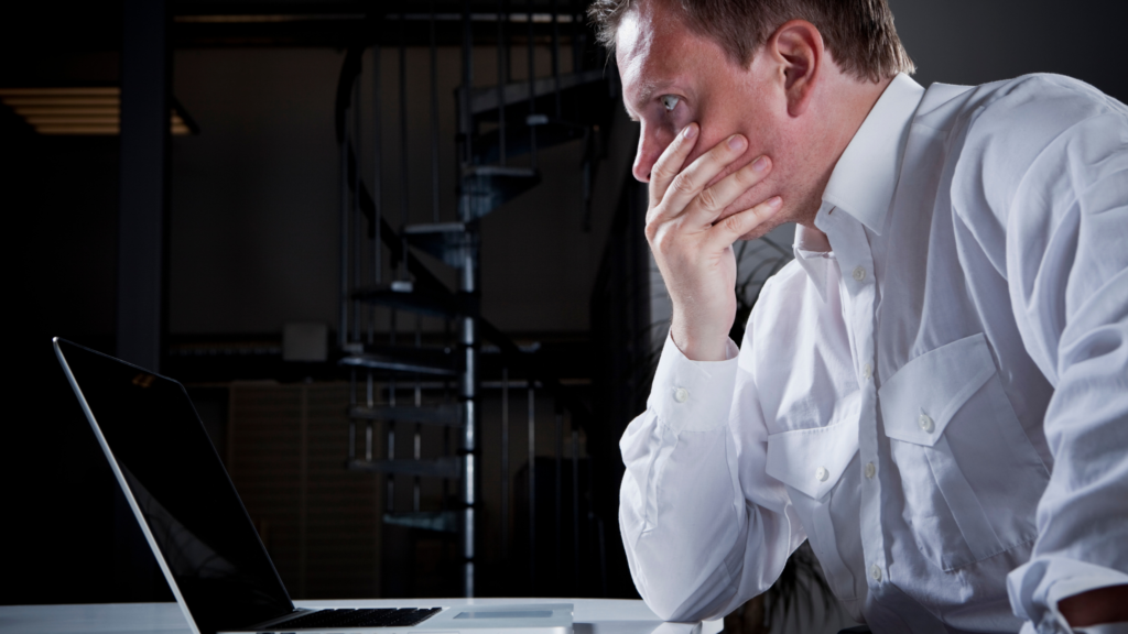 How to save a failing company. A businessman has a stressed look on his face and is looking at the screen of a laptop.