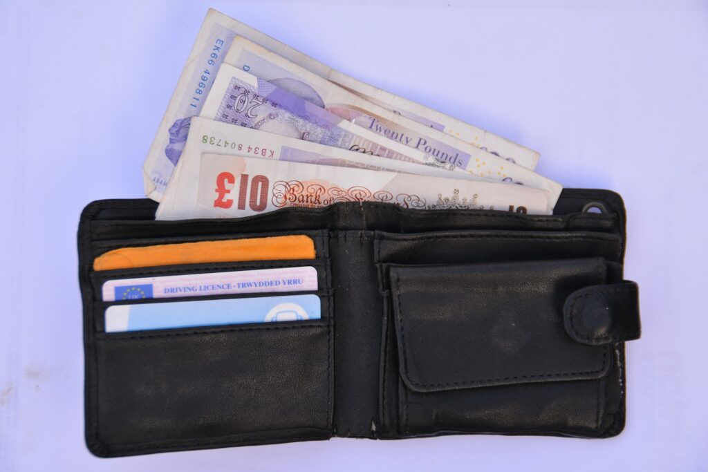 HMRC's debt-collecting arm. Four £20 notes and one £10 note falling out of an open wallet.