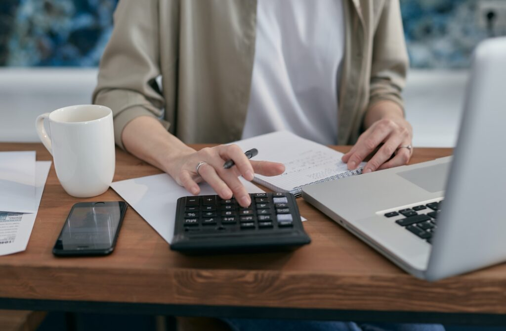 Taxing The SEISS. The image shows someone using a laptop and a calculator whilst writing in a notebook.