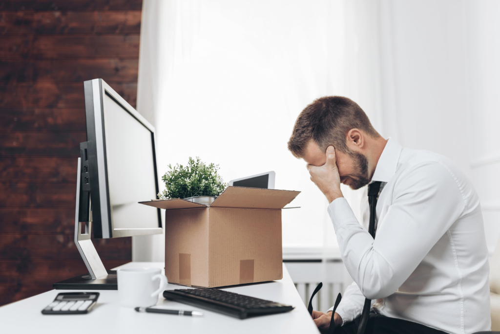 Furloughed employees. A man is crying in an office after packing the contents of his desk into a cardboard box.